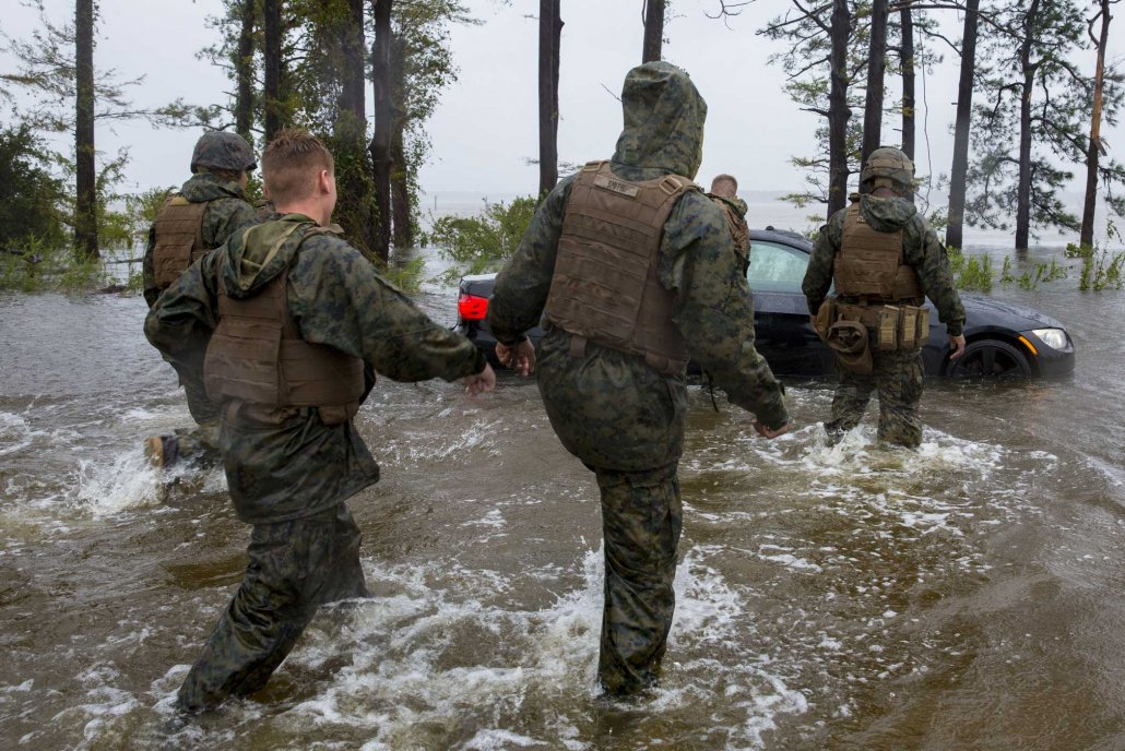 Marines help push a car out of a flooded area during Hurricane Florence, on Marine Corps Base Camp Lejeune in North Carolina in 2018. Hurricane Florence impacted MCB Camp Lejeune and Marine Corps Air Station New River with periods of strong winds, heavy rains, flooding of urban and low-lying areas, flash floods, and coastal storm surges. Photo by Lance Cpl. Isaiah Gomez, courtesy U.S. Marine Corps.