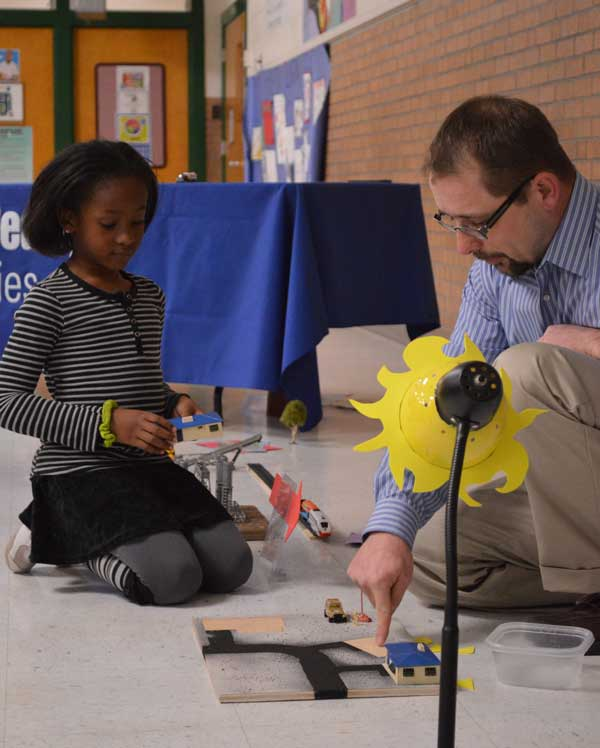 Naavah'sachi Joplin, a first grader at Logan Elementary School, and Mason Crawford, a volunteer science teacher, participate in an interactive energy demonstration at Logan Elementary School in 2013 highlighting Balfour Beatty Communities' solar energy project scheduled for military housing units at Fort Bliss. Photo by Sgt. Barry St. Clair, courtesy of U.S. Army.