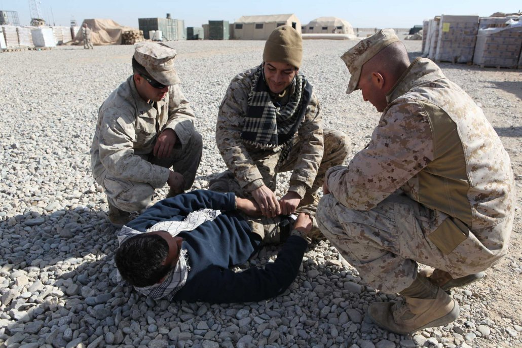 U.S. Marine Corps Lance Cpl. Kevin Rincon, left, and Lance Cpl. Zidan Sheabar, both with 2nd Platoon, Company I, Battalion Landing Team 3/8, teach interpreters attached to Company I how to apply a tourniquet at Forward Operating Base Price, Afghanistan, in 2011. Elements of 26th Marine Expeditionary Unit deployed to Afghanistan to provide regional security in Helmand province in support of the International Security Assistance Force. Photo by Gunnery Sgt. Bryce Piper, courtesy of U.S. Marine Corps.