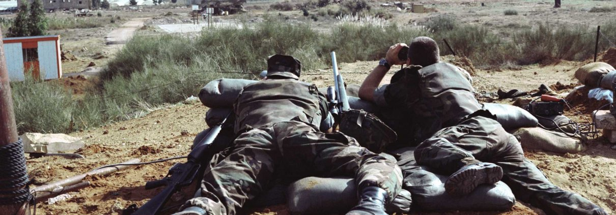 U.S. Marine sniper scouts use surveillance equipment to study the surrounding territory. Photo courtesy of U.S. National Archives.