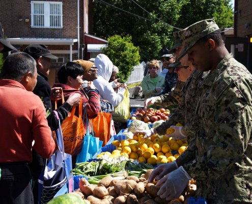 Sailors hand out food to local families during a community relations event at a Salvation Army site in Philadelphia in 2019. Community relations events could help lessen the military-civilian divide.