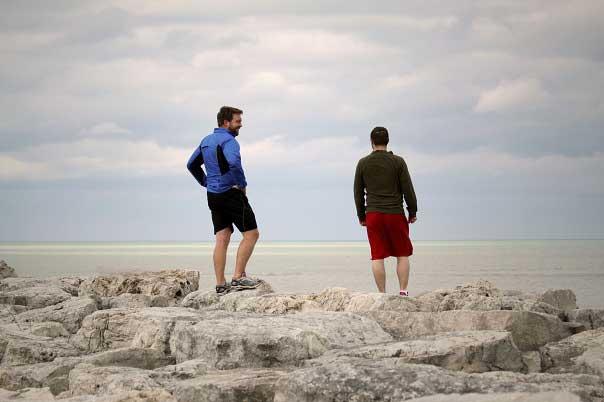 David Chrisinger, left, and Brett Foley hike along Lake Michigan.