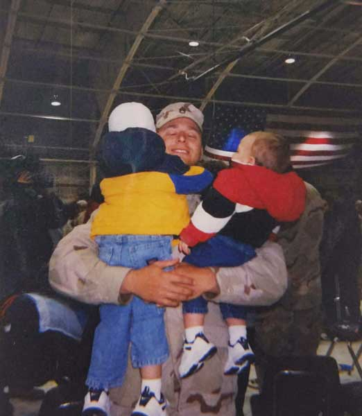 Tom Smoot hugs his kids during a homecoming ceremony in February 2004 after serving in Iraq. Photo courtesy of the author.