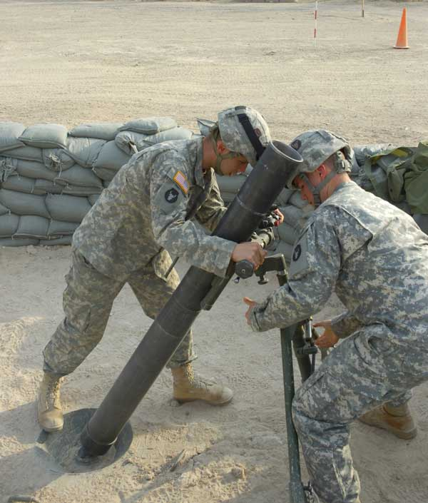 Spc. Jared Smith of Duluth, Minn., (left) and Spc. Lee Knutson of Oklee, Minn., both of Company B, 2nd Battalion, 136th Combined Arms Battalion, 1st Brigade Combat Team, 34th Infantry Division, man a mortar tube during a drill in 2006 at Camp Fallujah, Iraq.