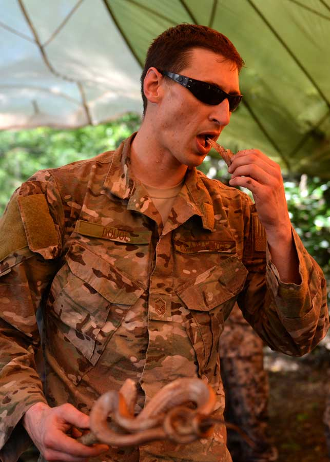 U.S. Air Force Master Sgt. Kurtis Douge, a survival, evasion, resistance, and escape specialist assigned to the 353rd Combat Training Squadron, eats a snake during survival training at Andersen Air Force Base, Guam, in 2017. Photo by Airman 1st Class Gerald R. Willis, courtesy of the U.S. Air Force.