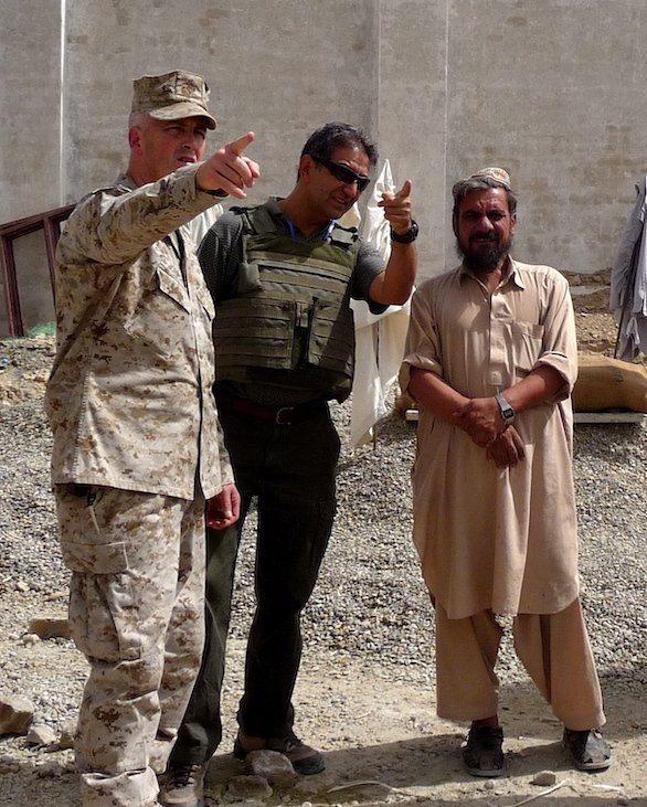 Atiqualla Rahin—an Afghan-American interpreter, U.S. Marine Chief Warrant Officer Bruce Johnson, and an Afghan contractor walk around the grounds of a new building site for a men's detention facility in Lashkar Gah in 2010. The facility was meant to accommodate men being held for trial in accordance with statutory law and rule of law procedures. Photo by Lt. j.g. Jennifer Franco, courtesy U.S. Navy.