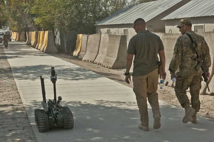A soldier and a contractor walk a Talon robot down Disney Drive in Afghanistan. Photo by Spc. Ken Scar, courtesy of U.S. Army.