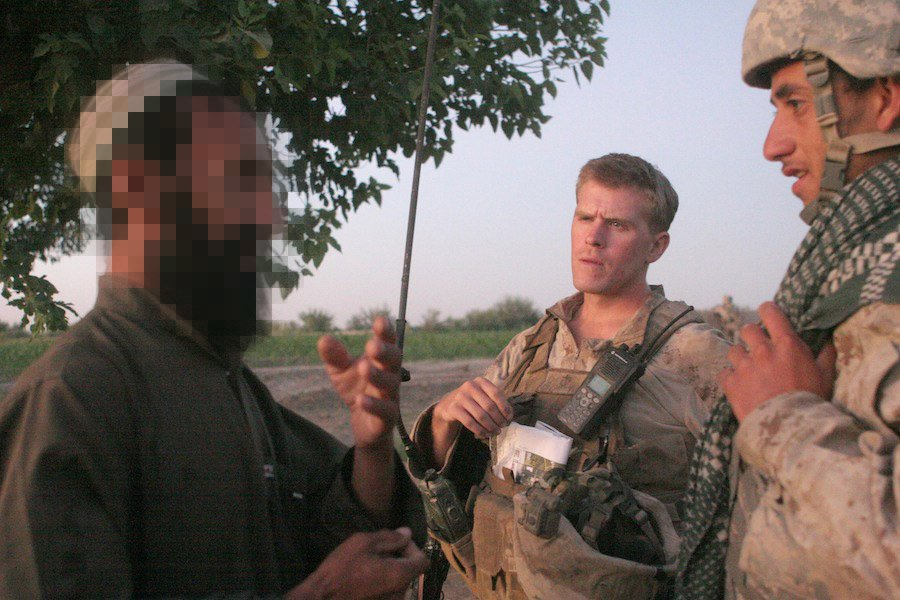 A farmer tells 1st Lt. Patrick O'Shea through an interpreter about a man who prematurely detonated an IED that critically injured two insurgents and a 5-year-old boy in 2009. The man, whose house the Taliban wanted to use to ambush the Marines, pulled a kite string attached to a detonator while insurgents placed a mine. Photo by Master Sgt. Chris W. Cox, courtesy of the U.S. Marine Corps.