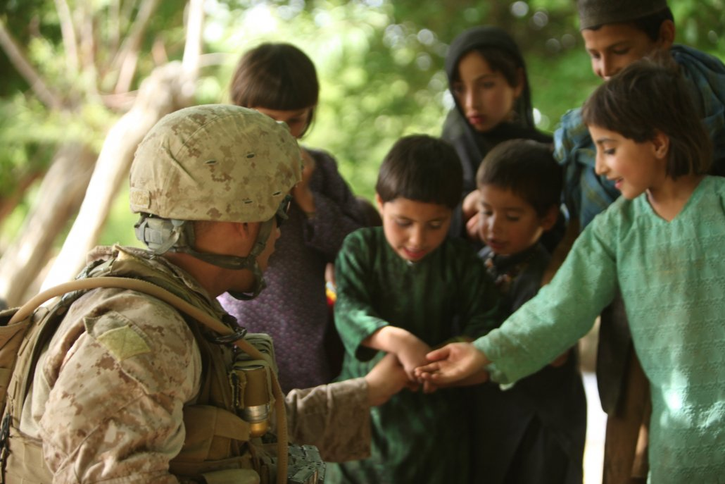 Lance Cpl. Jeremy Correa, infantryman, Golf Company, 2nd Battalion, 5th Marine Regiment, interacts with Afghan children while on a patrol through Musa Qa'leh District, Afghanistan, in 2012. Correa, from Elk Grove, Calif., was part of a patrol to disrupt insurgent supply lines and gain intelligence from locals. Photo by Cpl. Kenneth Jasik, courtesy of U.S. Marine Corps.