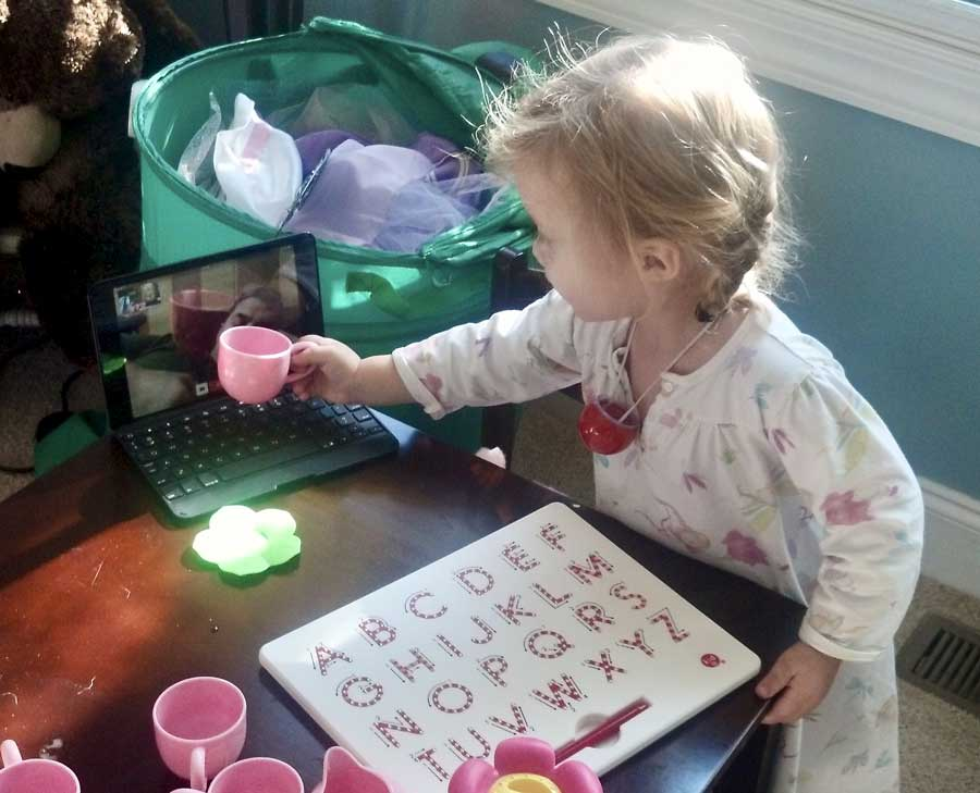 The author's then-three-year-old daughter having a Christmas tea party with her dad by Skype while he was deployed.