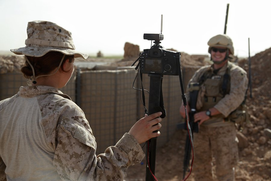U.S. Marine Corps Cpl. Lisa Tourtelot, combat correspondent with Marine Wing Headquarters Squadron 3, interviews Marine Corps Sgt. Joshua Wentzel, a heavy equipment operator with Marine Wing Support Squadron 273, at Combat Outpost Parselay, Helmand province, Afghanistan in 2012. Wentzel assisted in building a helicopter landing zone to reduce dust problems. Photo by Cpl. Meghan Gonzales, courtesy of U.S. Marine Corps.