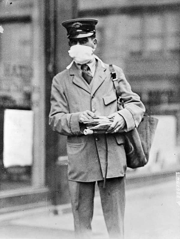 A New York City mailman goes about his business while wearing a gauze mask designed to stop infection during the fall of 1918. U.S. Army units mobilizing for World War I were struck hard by the virus, which often hit military bases first and then spread to civilians. Camp Upton on Long Island was closed to visitors in the fall of 1918 to prevent the spread of the flu. Photo courtesy New York National Guard.
