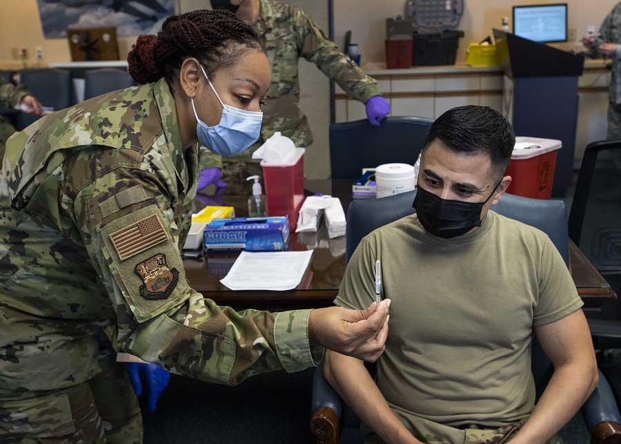 Capt. Shamira Conerly, 149th Medical Group, shows Master Sgt. David Romero, 149th Maintenance Squadron, the vaccine dose he will receive at Joint Base San Antonio-Lackland, Texas, March 18, 2021. Photo by Senior Airman Ryan Mancuso, courtesy U.S. Air National Guard.