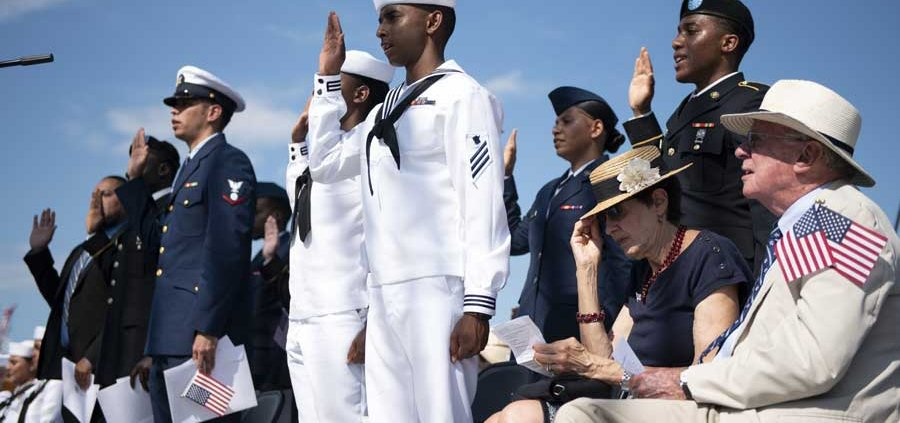 """Soldiers, sailors, airmen, a Coast Guardsman, and an Army veteran raise their right hands as they recite the oath of allegiance during a naturalization ceremony aboard USS Constitution in June. """"The United States is and will forever be a nation of immigrants,"""" Chief of Naval Operations Adm. Mike Gilday said during the ceremony. """"Your stories—and the cultures, customs, and traditions you bring to America—exemplify that we have more to unite us than to divide us."""" Photo by Mass Communication Spec. 1st Class Raymond D. Diaz III, courtesy of U.S. Navy."""