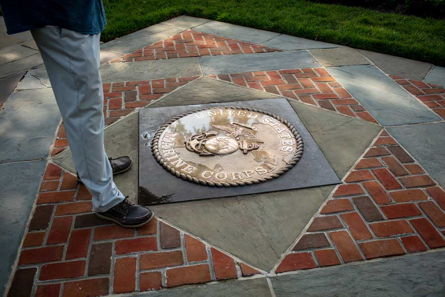 Robert Hogue stands beside the Marine Corps emblem on the patio at Marine Barracks Washington. Photo by Eliot Dudik, for The War Horse.