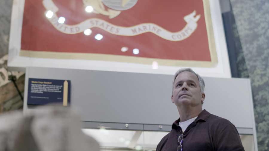 Robert Hogue stands beside the Marine Corps flag rescued from his office. Photo by Daniel Nelson, for The War Horse.
