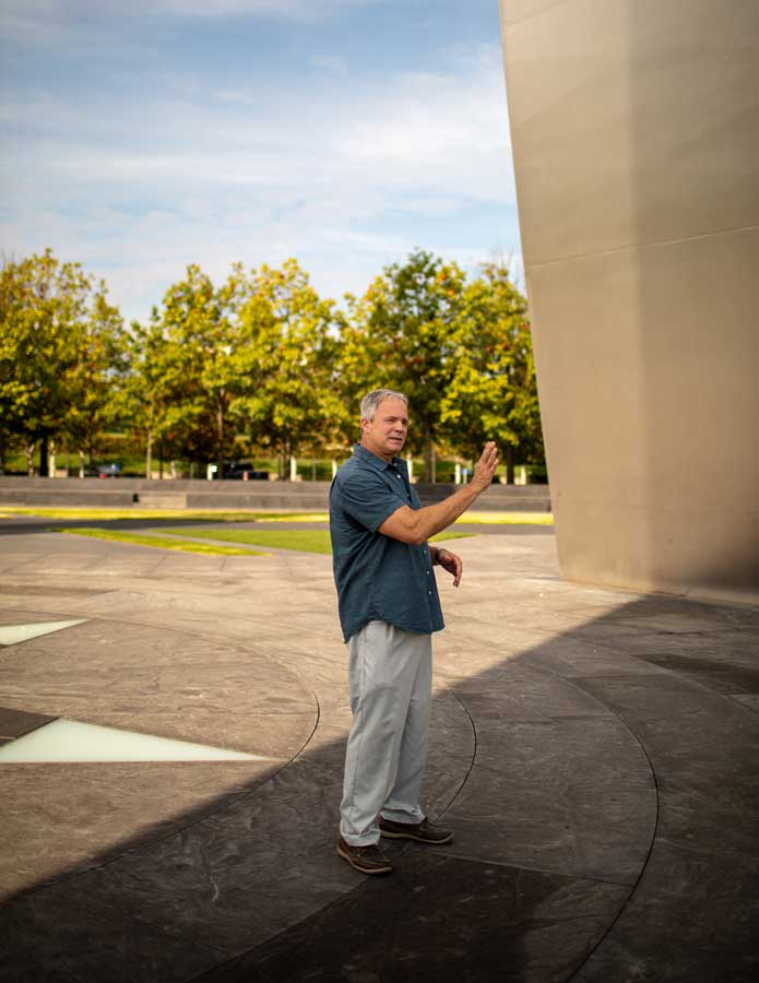 Robert Hogue explains the flight path of American Airlines Flight 77 as he stands beneath the U.S. Air Force Memorial in Arlington, Virginia. Photo by Eliot Dudik, for The War Horse.
