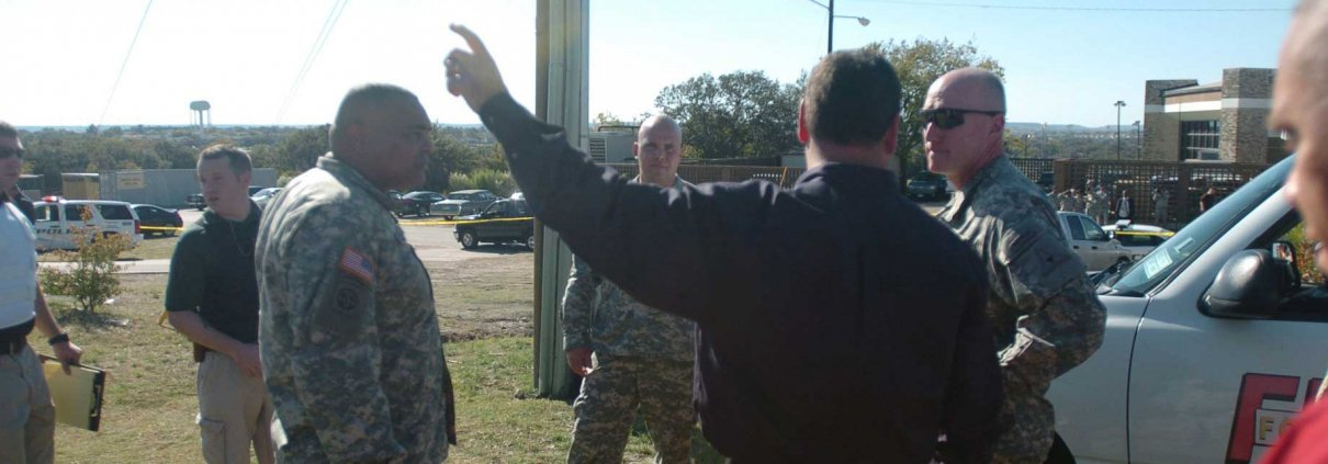 Lt. Gen Robert Cone (right), III Corps commanding general, and the corps' senior noncommissioned officer, Command Sgt. Maj. Arthur L. Coleman Jr., receive a briefing from Fort Hood law enforcement officers, including Eric Tangeman (center), outside the shooting site at Fort Hood. Thirteen people died and 30 more were wounded in the 2009 incident.