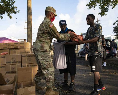 Louisiana National Guard 256th Infantry Brigade Combat Team Soldiers distribute food and water to citizens after Hurricane Ida, at Mahalia Jackson Theater, New Orleans, Louisiana, in September. Photo by Sgt. Renee Seruntine, courtesy U.S. Army National Guard.